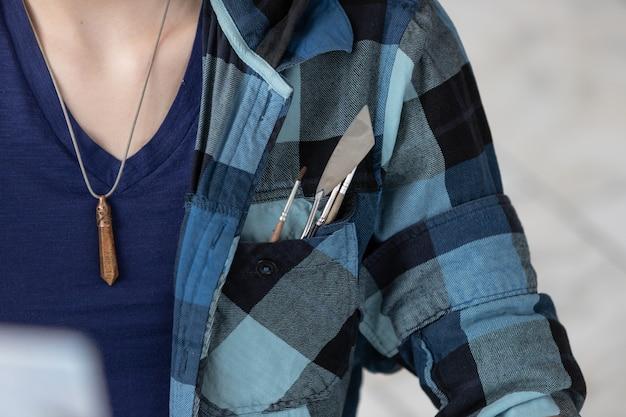 Kwasten en paletmes geplaatst in de zak van een geruit hemd. olieverf gereedschap.