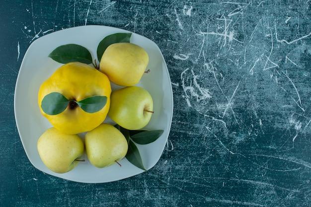 Kweepeer en appels op een bord, op de marmeren achtergrond. hoge kwaliteit foto