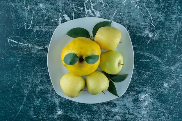 Kweepeer en appels op een bord, op de marmeren tafel.