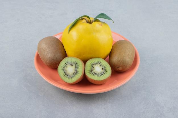 Kweepeer en gesneden kiwi's op oranje bord