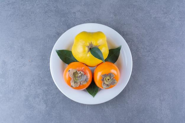 Kweepeer en persimmon fruit op plaat op marmeren tafel.
