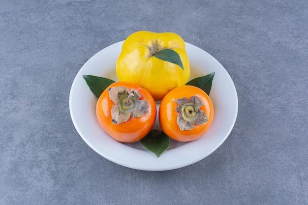 Kweepeer en persimmonvruchten op plaat op het donkere oppervlak