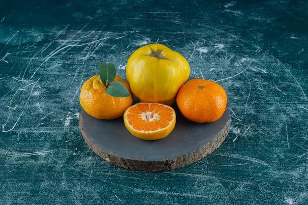Kweepeer en sinaasappelen op een bord, op de marmeren tafel.