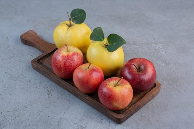 Kweeperen en appels gebundeld op een houten bord op marmeren achtergrond.