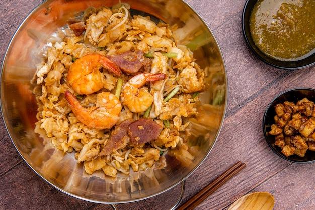 Kwetiau goreng medan of char kway teow het is gemaakt van noedels die worden geroerbakt in frituurolie met knoflookui of sjalotten varkensvlees gebakken garnaal gesneden bakso gehaktballetjes