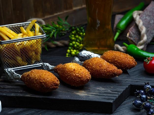 Kyiv cotletes met frietjes op houten bord