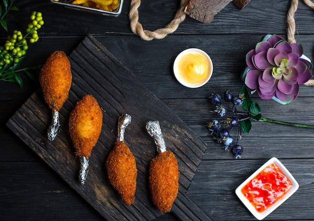 Kyiv cotletes met sauzen op houten bord