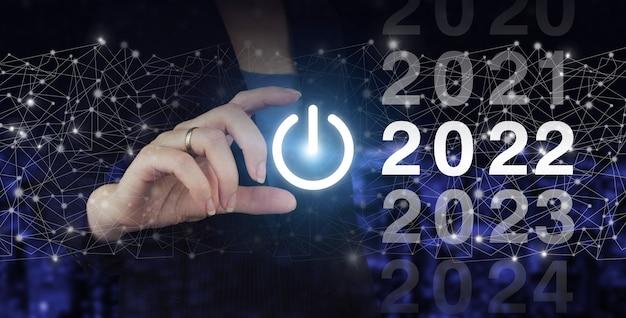Laadjaar 2021 t/m 2022. start concept. hand houden digitale hologram 2022 teken op stad donkere onscherpe achtergrond. concept start nieuwjaar 2022.