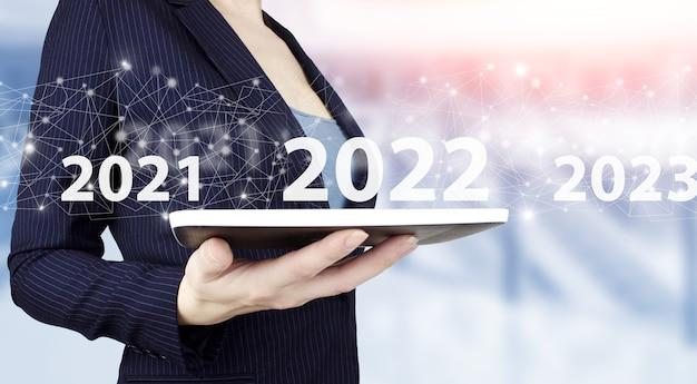 Laadjaar 2021 t/m 2022. start concept. hand houden witte tablet met digitaal hologram 2022 teken op lichte onscherpe achtergrond. concept start nieuwjaar 2022.
