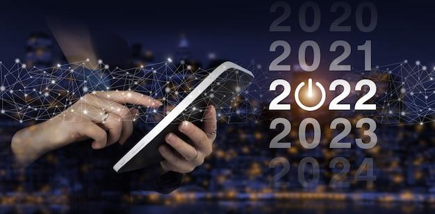 Laadjaar 2021 t/m 2022. start concept. witte tablet van de handaanraking met digitaal hologram 2022 teken op stads donkere onscherpe achtergrond. welkom jaar 2022. nieuwjaarskaart bedrijfsconcept.
