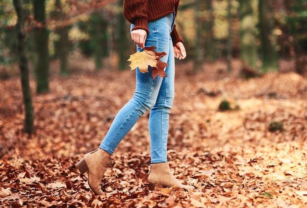 Laag deel van een vrouw die in het herfstbos loopt