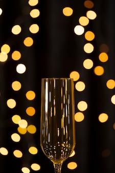 Laag hoek gouden licht en glas met champagne