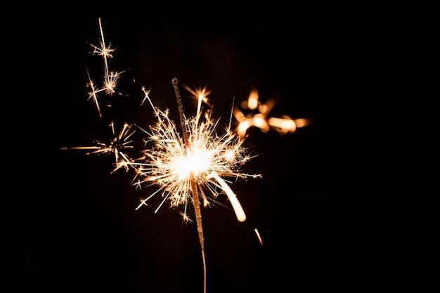 Laag hoek gouden vuurwerk bij nacht op hemel