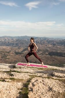 Laag hoek jong wijfje op berg die yoga doet