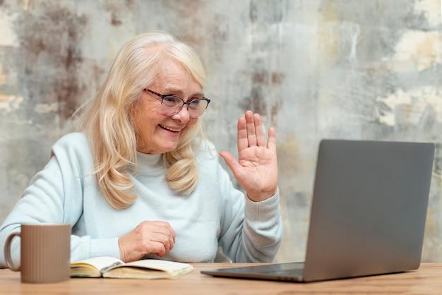 Laag hoek ouder wijfje dat aan laptop werkt