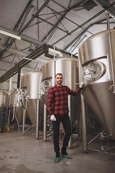 Laag hoek verticaal schot van een professionele brouwer die trots stelt bij zijn brouwerij