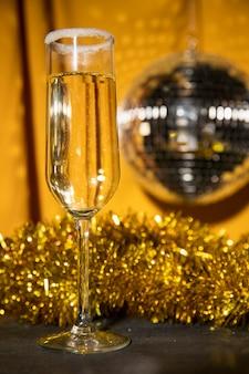 Laag hoekglas met champagne en zilveren feestbol