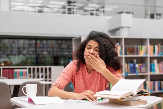 Laag hoekmeisje dat slaperig voelt bij bibliotheek