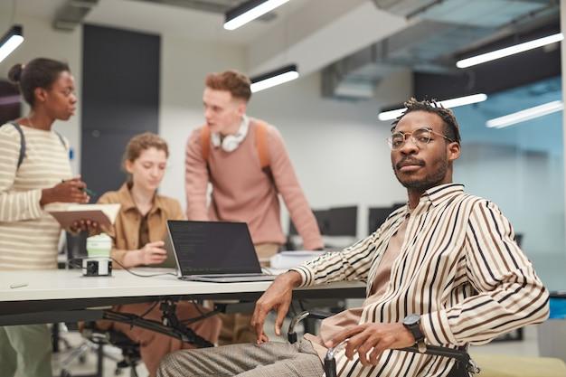 Laag hoekportret van een jonge afro-amerikaanse man die naar de camera kijkt terwijl hij een laptop gebruikt en met een groep mensen werkt, kopieer ruimte