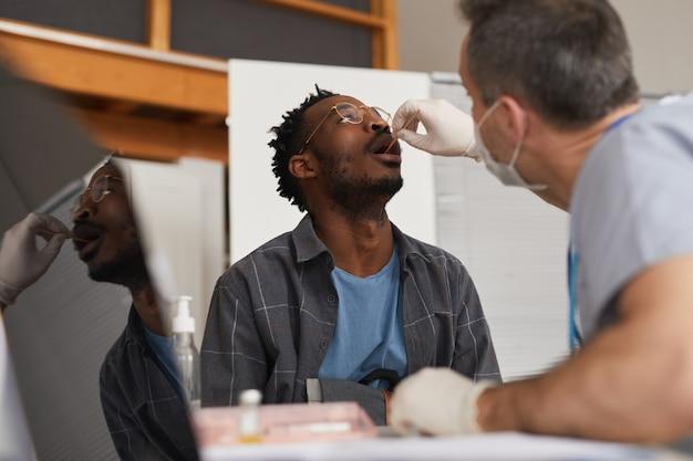 Laag hoekportret van jonge afro-amerikaanse man die covid-test doet in vaccinatiecentrum of kliniek, kopieer ruimte