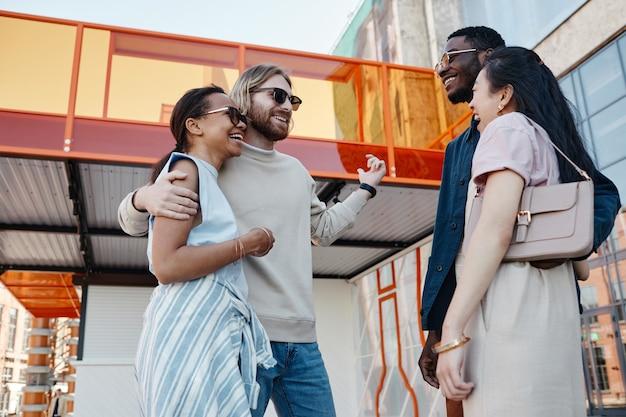 Laag hoekportret van twee stellen die elkaar buiten ontmoeten terwijl ze op dubbele date gaan in een stedelijke stadsomgeving