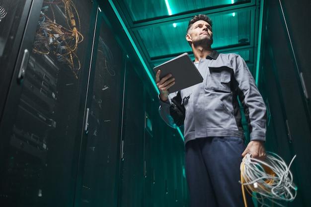 Laag hoekportret van volwassen netwerkingenieur die digitale tablet in serverruimte gebruikt tijdens onderhoudswerkzaamheden in datacenter, kopieer ruimte