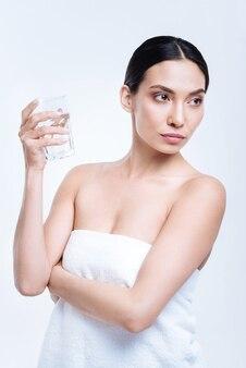 Laag hydratatieniveau. aangename donkerharige jonge vrouw die een glas water vasthoudt, op het punt staat het te drinken, terwijl ze in een handdoek wordt gewikkeld