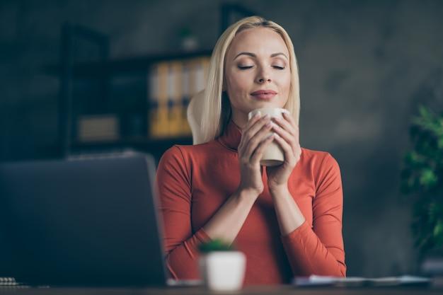 Laag onder de hoekfoto van een vrolijke schattige aardige vriendin die geniet van de geur van koffie met gesloten ogen en mok thee houdt die werkt voor transnationaal bedrijf