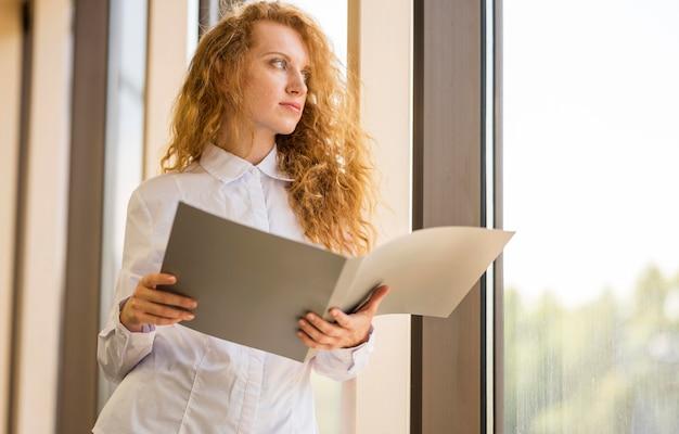 Laag uitzicht zakenvrouw kijkt buiten het raam