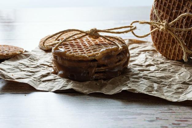 Laagdrempelige fotografie. close-up van een stapel stroopwafels met een sisalstrik, naast andere koekjes.