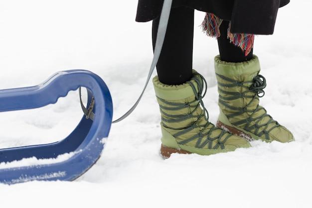 Laarzen in sneeuw en blauwe slee