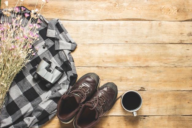 Laarzen, shirt, wilde bloemen, beker met thee, verrekijker op een houten ruimte. het concept van wandelen, toerisme, kamp, bergen, bos. banner.