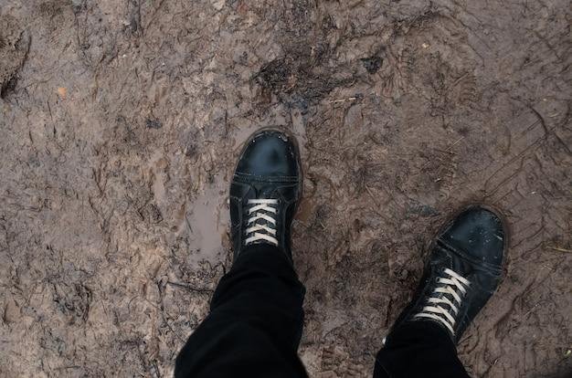 Laarzen staan in modder en smeltende sneeuw