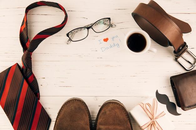 Laarzen tussen mannelijke accessoires in de buurt van cadeau en een kop met een drankje
