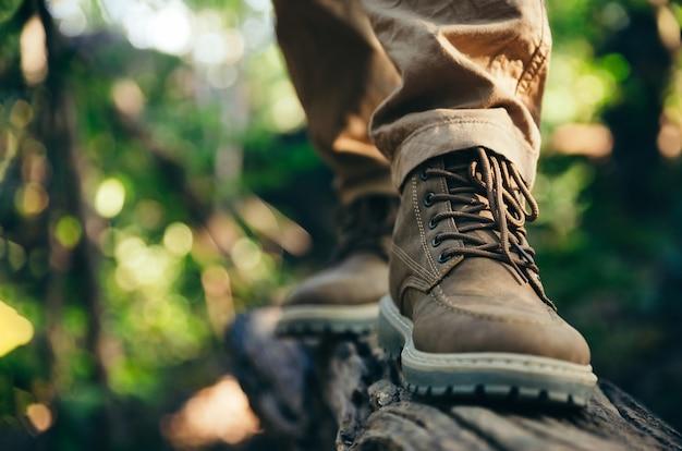 Laarzen van reizigerstap op oud logboek in bos.