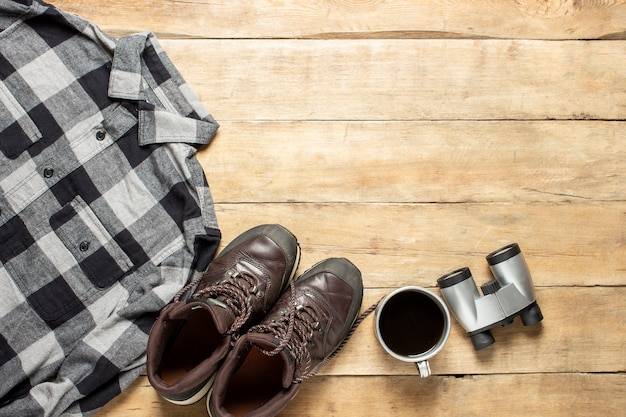 Laarzen voor een parcours, shirt, beker met thee, verrekijker op een houten achtergrond. concept van wandelen, toerisme, kamp, bergen, bos.