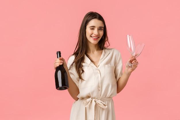 Laat dit feest beginnen. romantische vriendin die op haar partnerhuis wacht met twee glazen en fles champagne die sluw knipoogt en glimlacht, samen drinkt, lovelt date, roze muur heeft