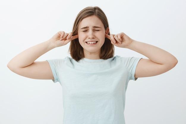 Laat dit geluid stoppen. ongelukkig onzeker huilend schattig meisje met bruin haar ogen sluiten en tanden op elkaar klemmen waardoor ontevreden trieste uitdrukking die oren bedekt met wijsvingers niet horen ouders vechten