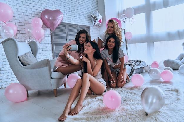 Laat een glimlach zien! vier aantrekkelijke jonge vrouwen in pyjama die glimlachen terwijl ze selfies maken in de slaapkamer met overal ballonnen