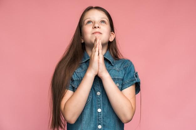 Laat me alsjeblieft. portret van schattig klein meisje hand in hand in gebed gebaar en toestemming vragen, bidden over iets. indoor studio-opname geïsoleerd op roze background