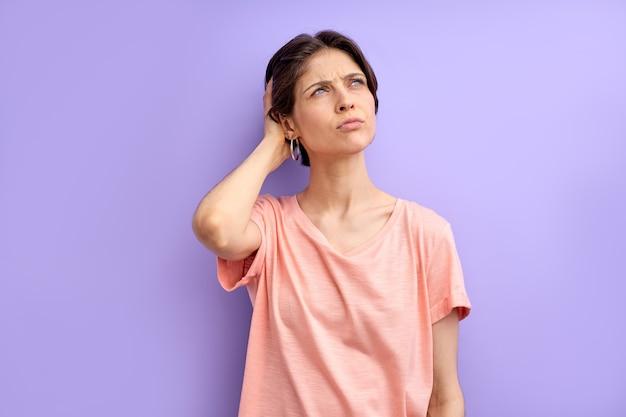Laat me denken aan een jonge kortharige vrouw die in contemplatie denkt en haar hoofd aanraakt, geconcentreerd op hoewel...