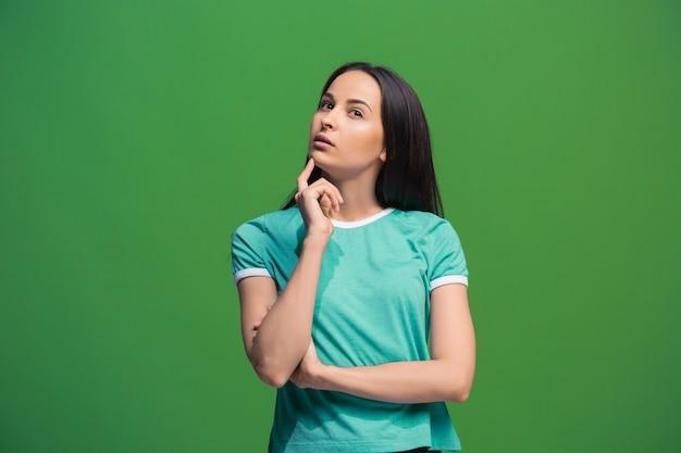 Laat me denken. twijfel concept. twijfelachtige peinzende vrouw die met doordachte uitdrukking keuze maakt. jonge emotionele vrouw. menselijke emoties, gezichtsuitdrukking concept. voorkant . studio. geïsoleerd op trendy groen