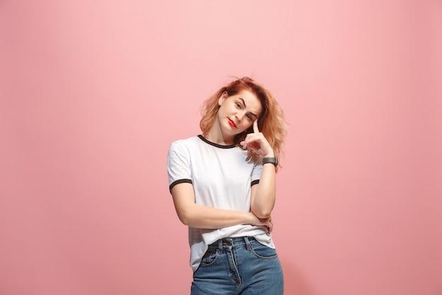 Laat me denken. twijfelachtige peinzende vrouw die met nadenkende uitdrukking keus tegen roze muur maakt