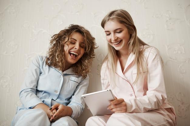 Laat me je een grappige video laten zien. portret van mooie kaukasische blonde zus in nachtkleding vrije tijd doorbrengen met vriend, digitale tablet te houden tijdens het lezen van hilarische grap of artikel, samen plezier