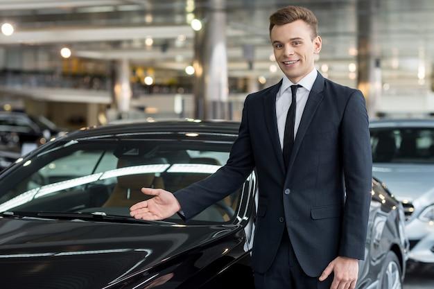 Laat me ons nieuwe model laten zien. knappe jonge klassieke autoverkoper die bij de dealer staat en auto wijst