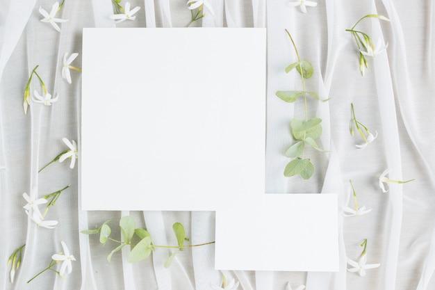 Laat takjes en jasminum auriculatum bloemen met trouwkaart op sjaal