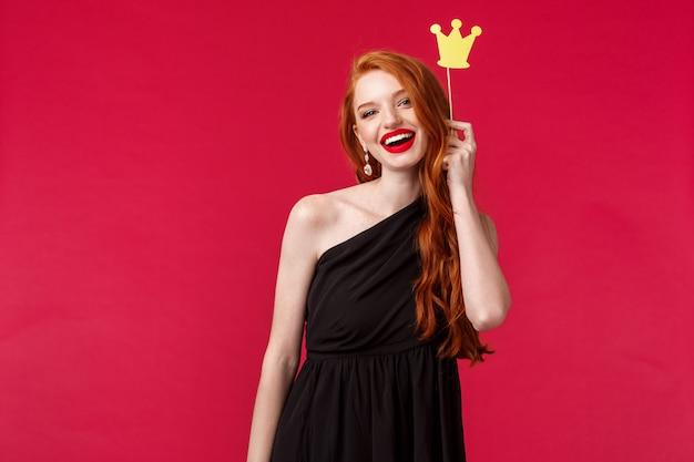 Laat zien wie koningin is. schattige roodharige blanke vrouw in luxe zwarte jurk, rode lippenstift, kroon op stok houden en glimlachen, plezier maken met vriendinnen avondje uit, op een rode muur