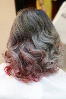 Laatste gekleurde tips kort haar na geverfd met rood en ijzer golvend in salon