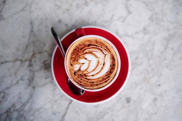 Laatste kunst, rosettabloem op een schuimende cappuccino, op een rode kop in een café.