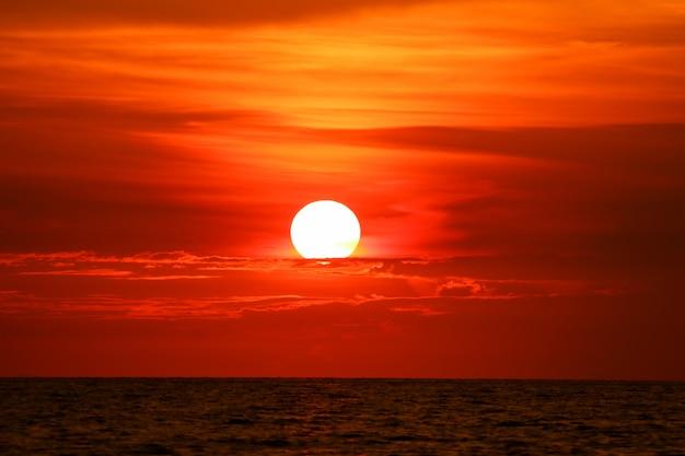 Laatste licht van zonsondergang op hemelwolkstraal rond zon over overzees